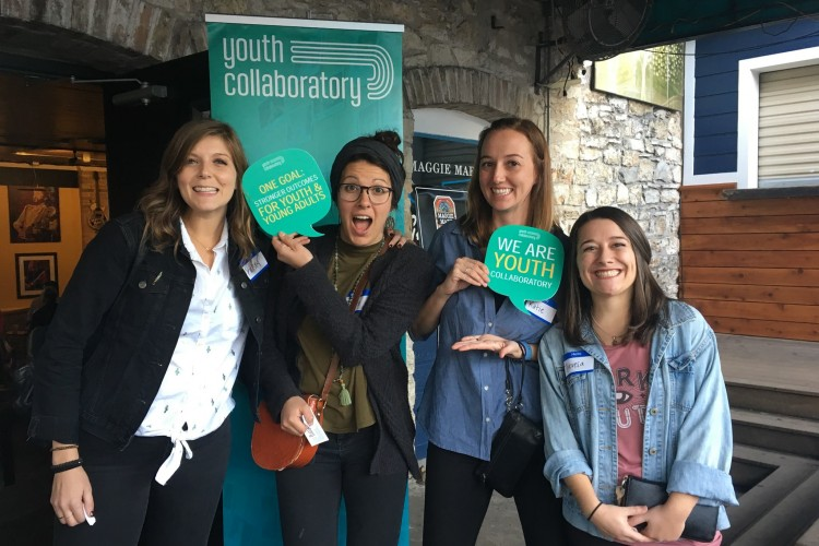 group of people posing with youth collaboratory signs