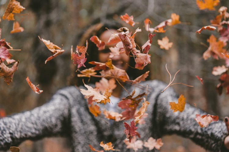 Person throwing leaves in the air